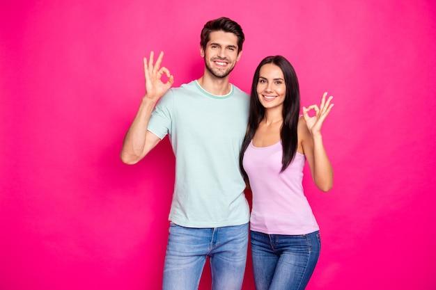 La foto del ragazzo e della signora divertenti delle coppie che sollevano le mani che mostrano i simboli okey che approvano le risposte positive portano i vestiti casuali isolati il fondo di colore rosa brillante