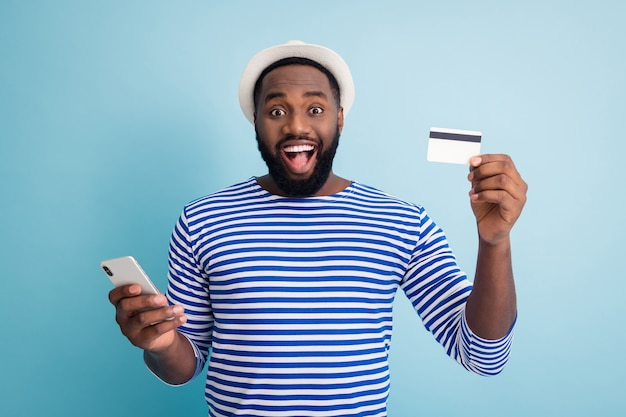 Foto di divertente pelle scura ragazzo tenere telefono app navigazione fare acquisti online utilizzare fresco servizio carta di credito indossare berretto da sole bianco camicia da marinaio a strisce isolato muro di colore blu