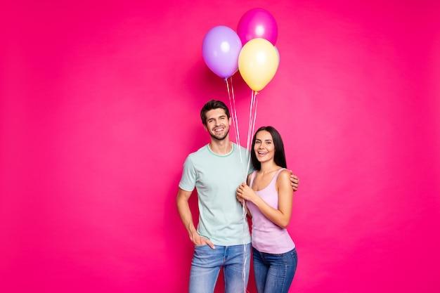 La foto delle coppie divertenti della signora e del ragazzo che tengono gli aerostati di aria nelle mani è venuta alla festa di compleanno dei genitori indossare abbigliamento casual isolato sfondo rosa