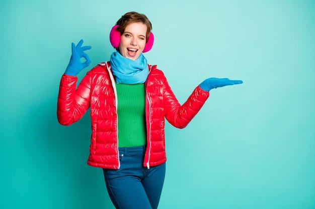 Foto di donna divertente tenere a braccio aperto novità prodotto fresco offerta mostra okay simbolo occhiolino indossare casual cappotto rosso sciarpa blu copri orecchie rosa pantaloni maglione isolato verde acqua muro di colore