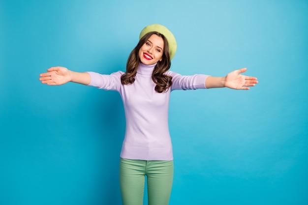 Foto del viaggiatore divertente signora buon umore abbracci aperti incontrare il migliore amico aeroporto indossare moderno berretto verde cappello viola maglione a collo alto pantaloni isolati parete di colore blu