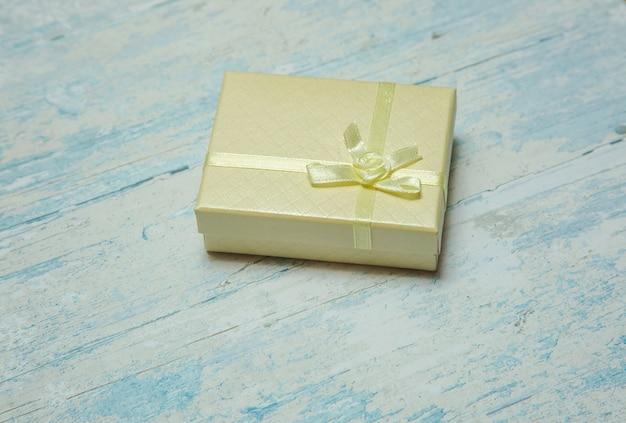 Confezione regalo con foto con fiocco su sfondo strutturato in legno blu vista dall'alto dal lato