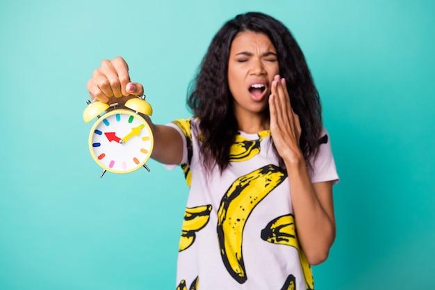Foto di una ragazza che mostra la sveglia che sbadiglia con il palmo della bocca aperta indossa una maglietta con stampa di banane e uno sfondo di colore verde acqua isolato