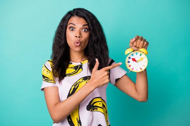 La foto della ragazza indica che la sveglia tiene la sveglia con il braccio del dito che indossa una maglietta con stampa a banana isolata sullo sfondo di colore turchese
