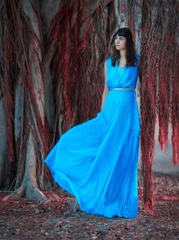 Foto di una ragazza con un lungo vestito blu elegante.