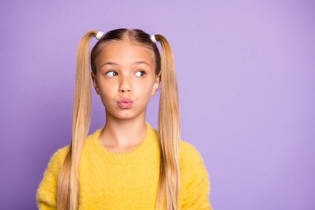 La foto della ragazza che esamina lo spazio vuoto con le sue labbra ha imbronciato la parete viola pastello isolata di colore
