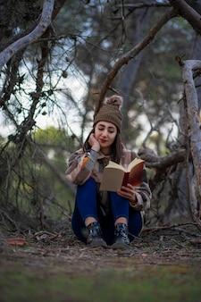 Foto di una ragazza che legge un libro nella foresta in una giornata invernale