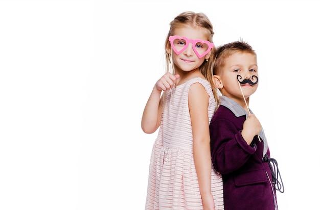 Foto di una ragazza con gli occhiali di cartone a forma di cuore e un ragazzo con i baffi di cartone in posa