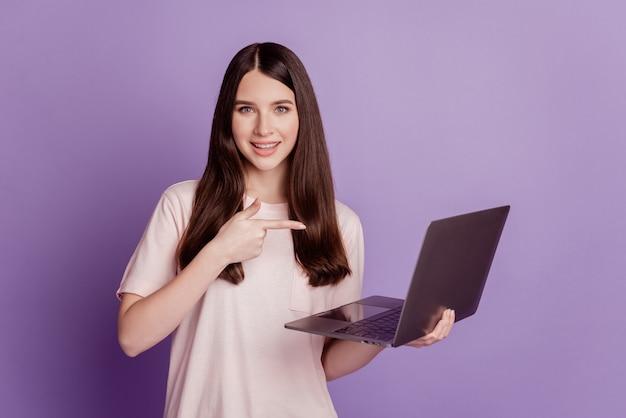Foto di una ragazza con un dispositivo portatile a dito diretto su sfondo viola