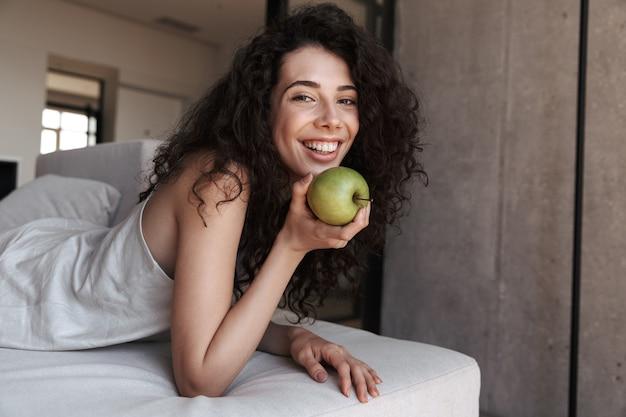Foto di splendida donna riccia con lunghi capelli scuri che indossa abiti di seta per il tempo libero che mangia mela verde fresca con piacere e sorriso, mentre giaceva sul divano di casa