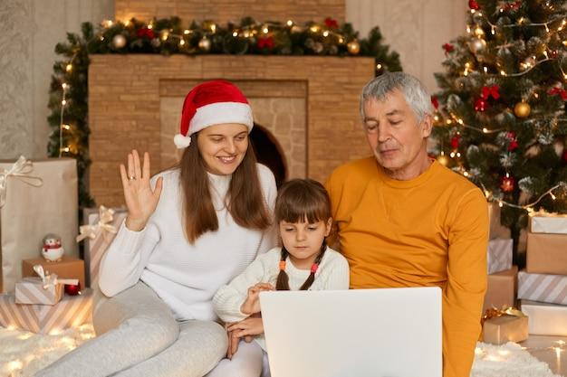 Foto del nonno, della mamma e del bambino che fanno la videochiamata della vigilia di natale