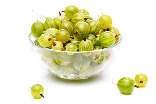 Foto di uva spina verde in tazza di vetro su sfondo bianco vuoto in studio