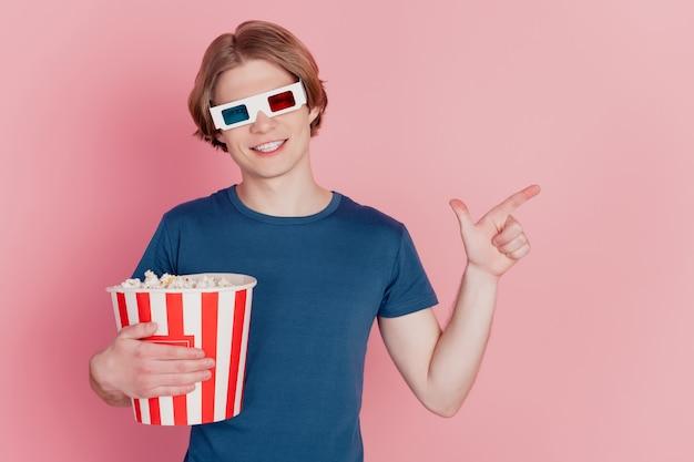 Foto di un ragazzo che tiene popcorn felice sorriso positivo indossa occhiali 3d punta il dito spazio vuoto annuncio consiglio isolato sfondo rosa colore