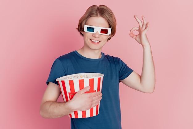 Foto di un ragazzo che tiene in mano una scatola di carta per popcorn felice sorriso positivo indossa occhiali 3d mostra ok alrigth cartello pubblicitario isolato sfondo di colore rosa