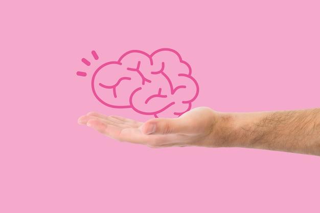 Mano della foto che tiene un cervello dell'illustrazione minimo in uno sfondo rosa