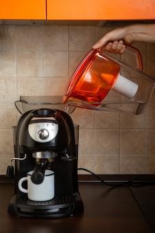 Foto della mano dell'uomo che versa acqua dalla brocca nella caffettiera in cucina