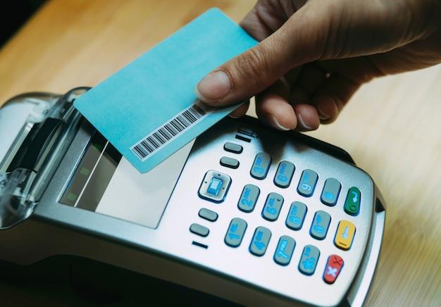 Foto della donna della mano che paga con la carta di credito con paypass