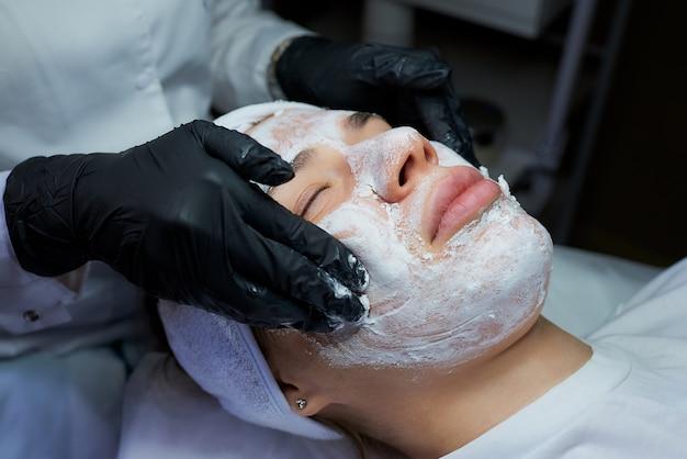 Una foto delle mani del cosmetologo femmina rimuove il gommage sbucciante dal viso della donna