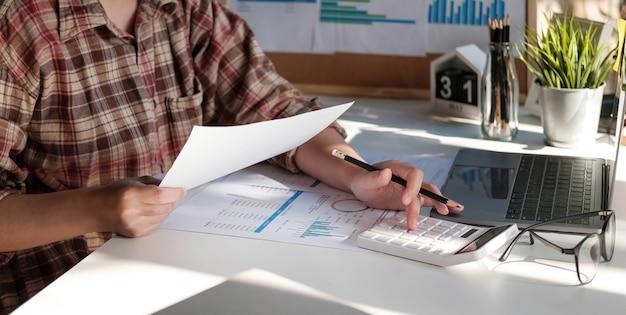 Foto di mani che tengono la penna sotto il documento e premono i pulsanti della calcolatrice