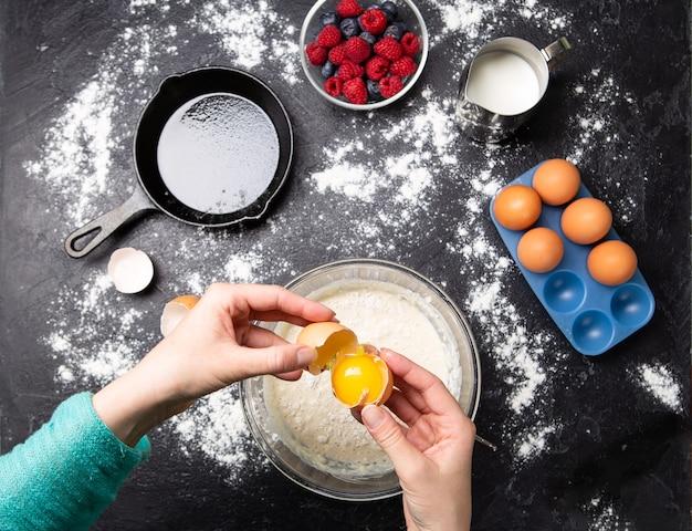 Foto delle mani dell'uomo che rompe le uova nella ciotola. tavolo con frutti di bosco, latte, farina. foto dall'alto