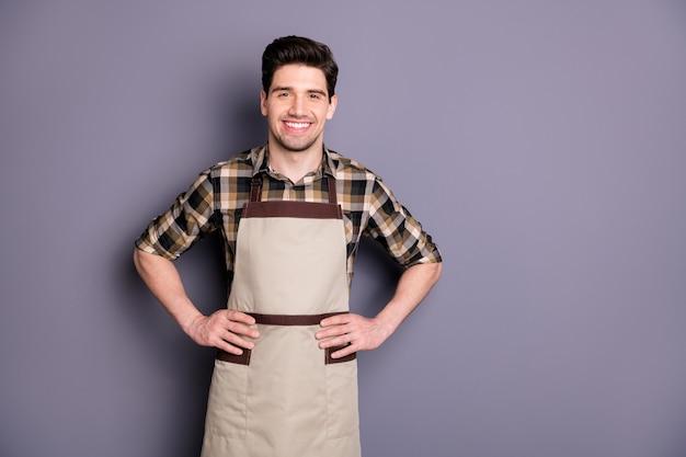 Foto di bel ragazzo brunet braccia dai lati sorridente amichevole che invita i visitatori su aroma caffè lavoratore professionista indossare camicia a quadri grembiule isolato muro di colore grigio
