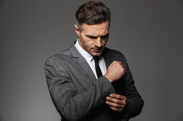 La foto dell'uomo d'affari bello che indossa il vestito di affari fissa il gemello o il bottone sulla manica della giacca classica, isolata sopra la parete grigia