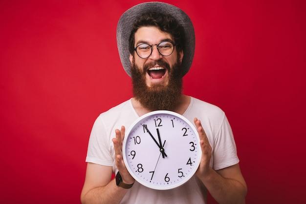 Foto di un bell'uomo barbuto eccitato, con indosso un cappello da cowboy, con in mano l'orologio in piedi su sfondo rosso