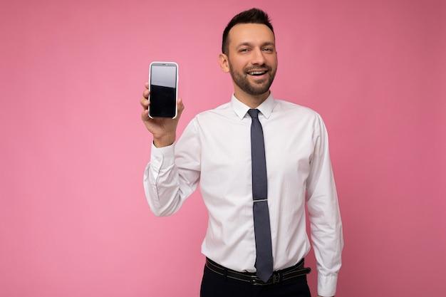 Foto di bell'uomo di bell'aspetto che indossa camicia bianca casual e cravatta isolato su sfondo rosa