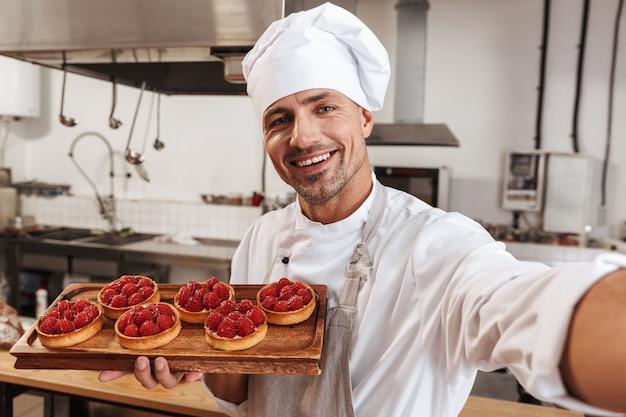Foto del bel capo maschio in uniforme bianca prendendo selfie e tenendo il piatto con le torte