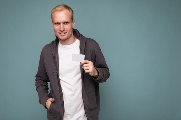Foto di bell'uomo biondo sicuro di sé che indossa un maglione grigio e maglietta bianca isolata sopra