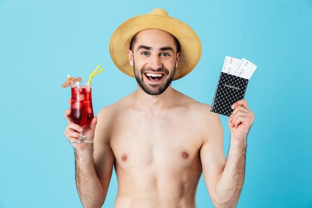 Foto di un bel turista a torso nudo che indossa un cappello di paglia che sorride mentre tiene in mano un cocktail e biglietti di viaggio con passaporto isolato
