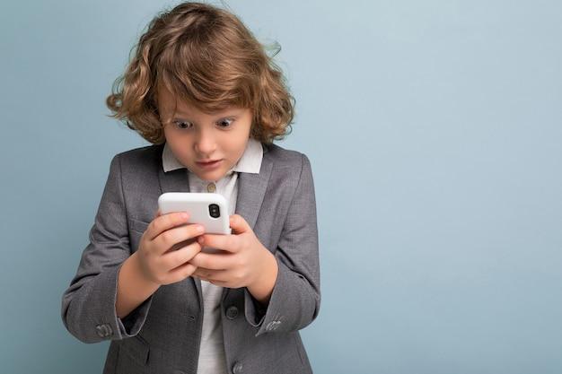 Foto del ragazzo scioccato bello con i capelli ricci che porta vestito grigio che tiene e usando il telefono
