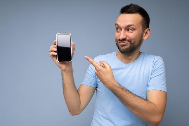 Foto di bello sorridente persona di sesso maschile adulto bello che indossa abbigliamento casual in piedi isolato su