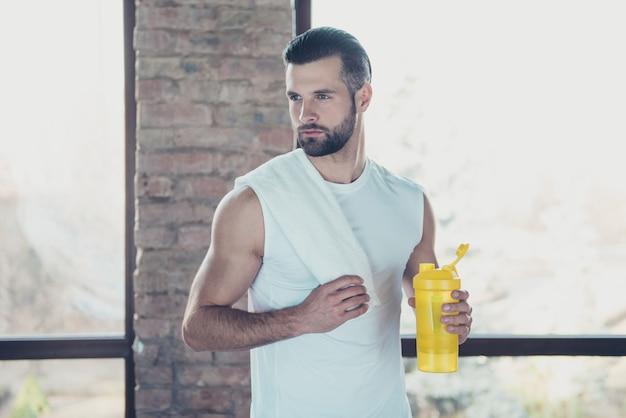 La foto del bel ragazzo sportivo ha terminato l'allenamento mattutino bevendo acqua fresca tenendo l'asciugamano guardando le finestre della casa di addestramento della canotta sportiva laterale concentrata all'interno
