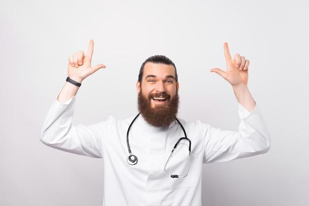 Foto di un bel giovane medico adulto che sorride e indica il copyspace