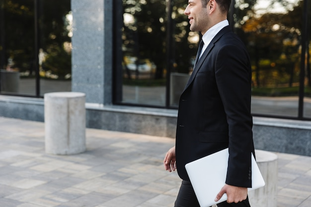 Foto di bel giovane imprenditore camminare all'aperto in strada con il computer portatile.