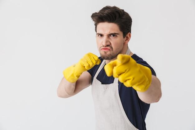 Foto di un bel giovane che indossa guanti di gomma gialli per la protezione delle mani che puntano le dita contro copyspace mentre pulisce la casa isolata su bianco