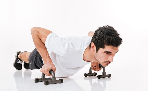 Foto di bel giovane sportivo in palestra fare esercizio di flessioni sul pavimento sopra il muro bianco.