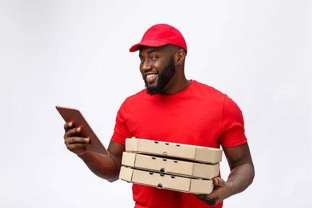 Foto dell'uomo afroamericano felice dal servizio di consegna in maglietta rossa e cappuccio che danno l'ordine dell'alimento e che tengono le scatole della pizza