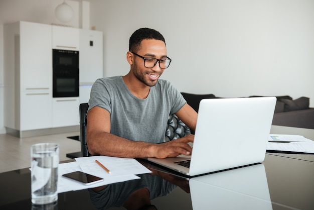 Foto di un uomo africano felice vestito con una t-shirt gey e con gli occhiali usando il laptop e seduto al tavolo.