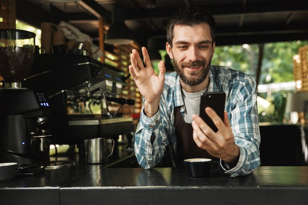 Foto di un barista felice che indossa un grembiule che sorride mentre usa lo smartphone al bar o al caffè all'aperto