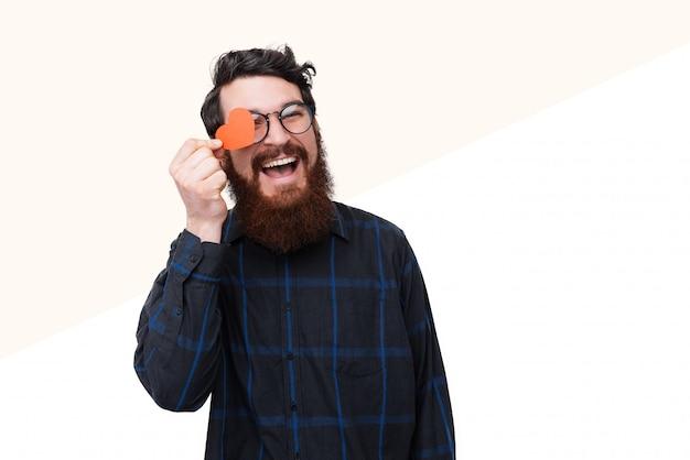 Foto di felice ragazzo barbuto isconing occhio con cuoricino di carta