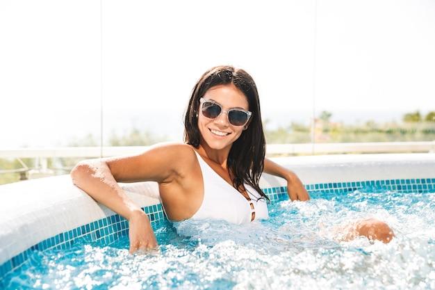 Foto di bella donna felice in costume da bagno bianco e occhiali da sole che si siede nella vasca idromassaggio jacuzzi, nella zona di hotel di lusso durante le vacanze