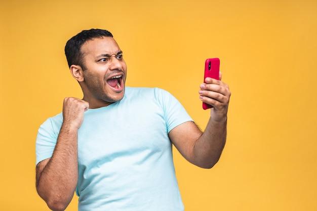 Foto di un uomo indiano afroamericano nero felice sapendo di essere diventato vincitore di qualcosa di così gioioso godendosi le informazioni sulle notizie mentre era isolato su sfondo giallo. usando il telefono.