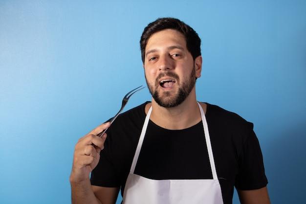 Foto dell'uomo felice del cuoco unico che tiene l'utensile per cucinare la carne