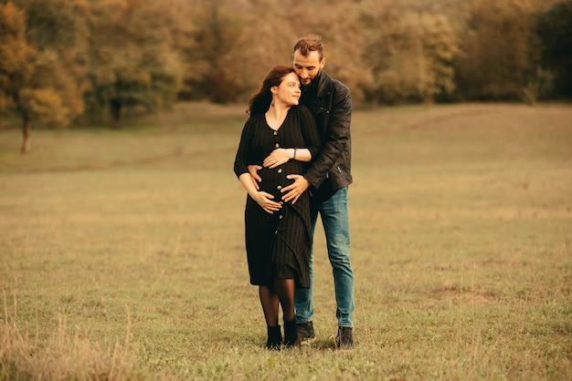 Foto dei futuri genitori delle coppie felici sulla passeggiata nel parco, abbracciando da dietro