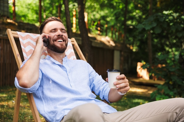 Foto dell'uomo europeo felice che ride e che si siede nella sedia a sdraio con caffè da asporto durante il riposo nel parco