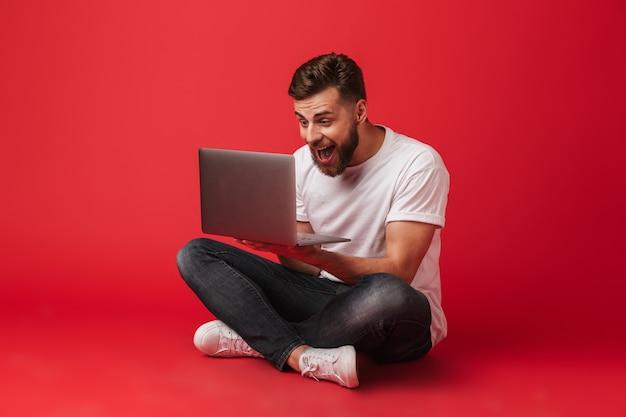 Foto di felice uomo eccitato in t-shirt e jeans seduto sul pavimento e urlando come fortunato ragazzo o vincitore mentre guarda sul laptop, isolato su sfondo rosso