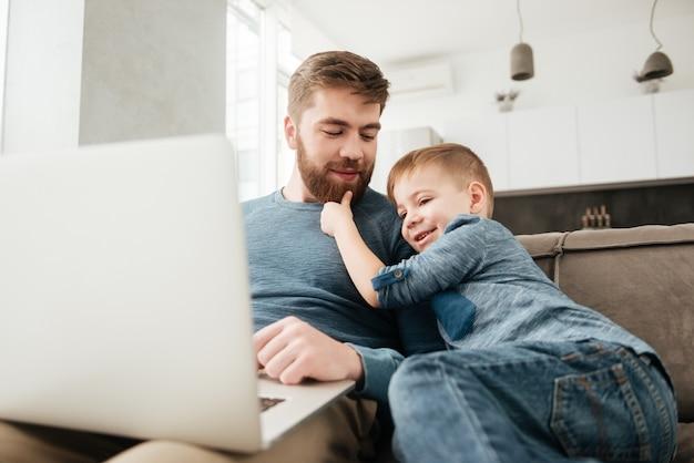Foto del padre felice che utilizza il computer portatile con il suo piccolo figlio carino.