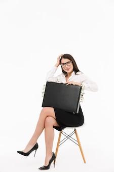 Foto di una donna d'affari lavoratrice felice vestita con abiti formali che tiene in mano una valigetta piena di banconote da un dollaro mentre è seduta su una sedia isolata su un muro bianco